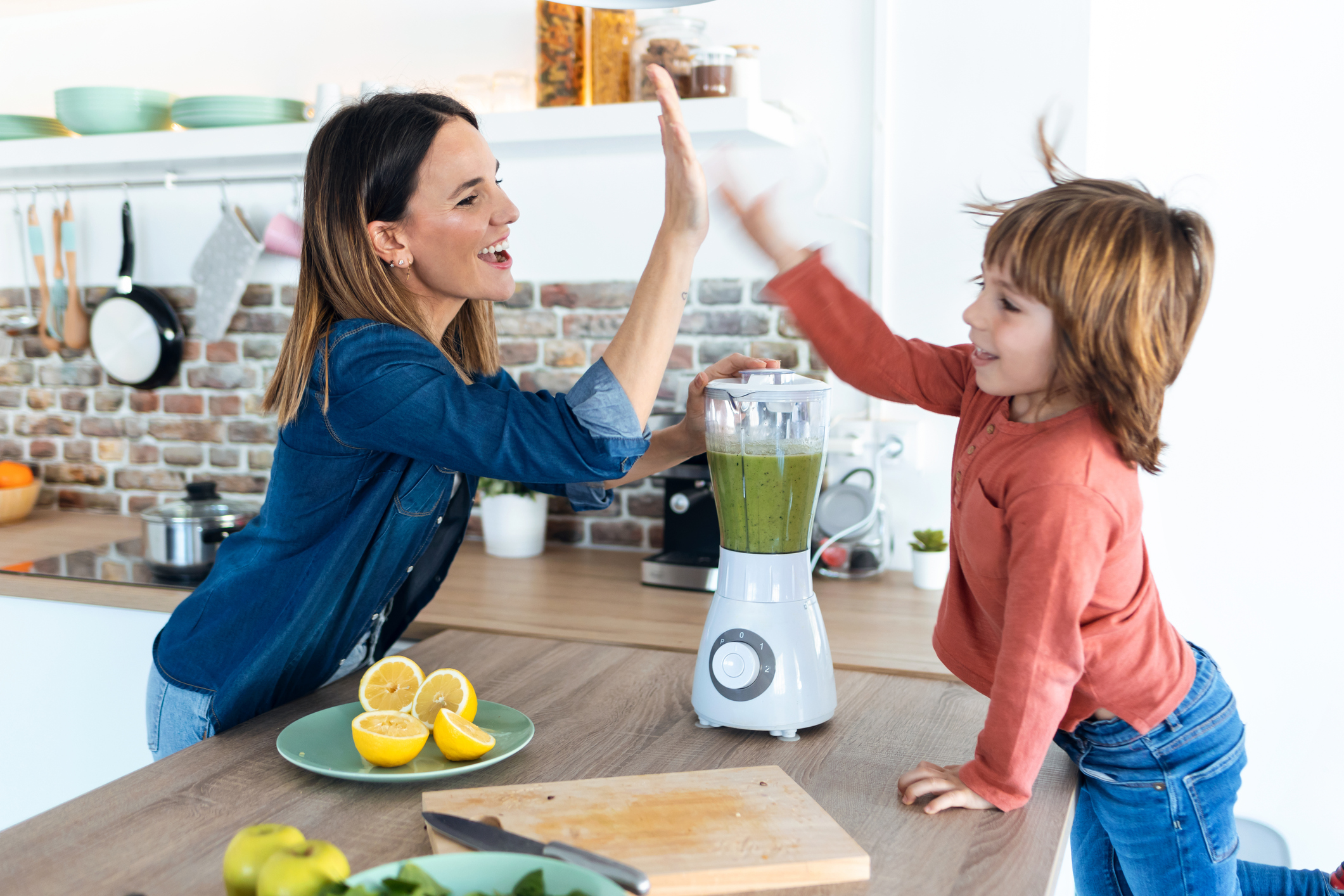 Pretty young mother and her son giving high five after preparing a detox smoothie together in the kitchen at home.